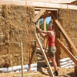 Sally plumbs the door jam of her straw bale studio.